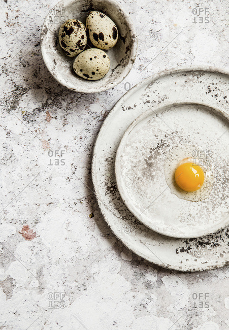 Cracked quail egg on a grey ceramic plates, few eggs in a small grey bowl, grey background.