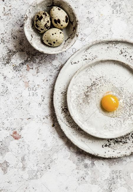 Cracked quail egg on a grey ceramic plates, few eggs in a small grey bowl, grey background.
