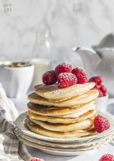 Ricotta pancakes with raspberries, dusted with icing sugar.