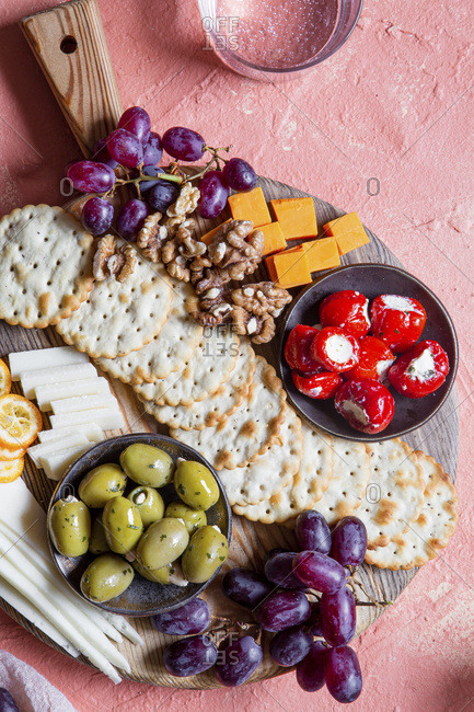 A cheese board with grapes, rosemary crackers, olives, stuffed mini peppers and walnuts
