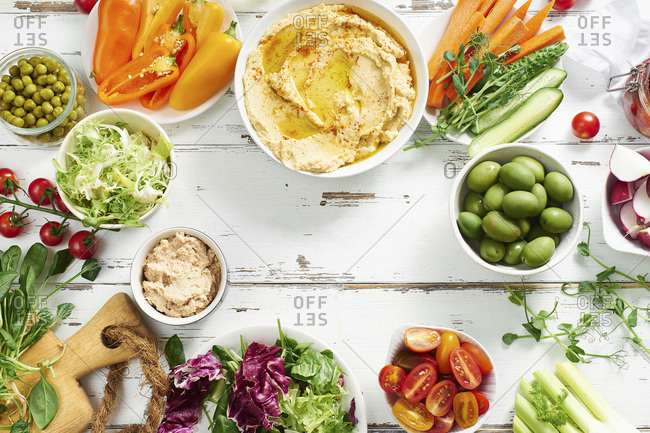 Hummus dip and raw vegetarian snacks on white wooden table. Copy space