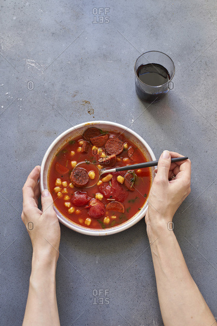 Female hands holding a bowl of tomato soup with chickpeas, chorizo sausage and parsley