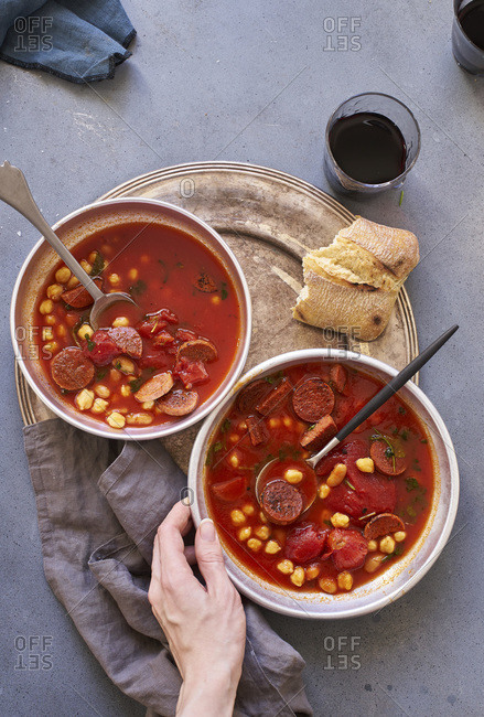 Two bowls of tomato soup with chickpeas, chorizo sausage and parsley with a glass of wine