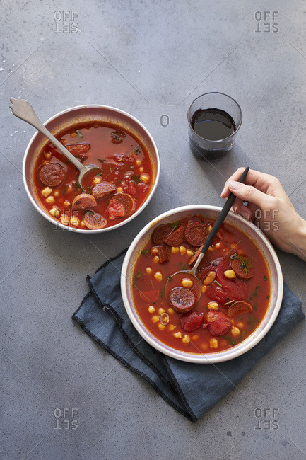 Overhead image of two bowls of tomato soup with chickpeas, chorizo sausage and parsley