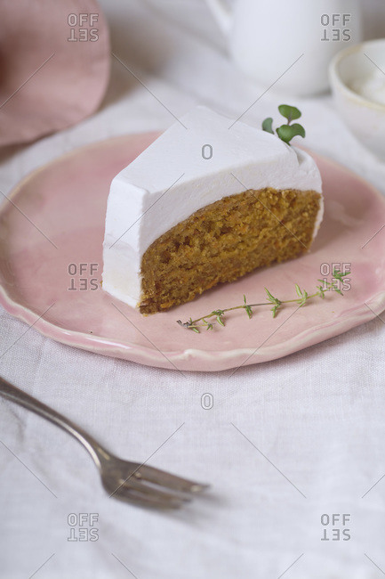 Vegan carrot cake slice with coconut cream frosting served on a pink plate