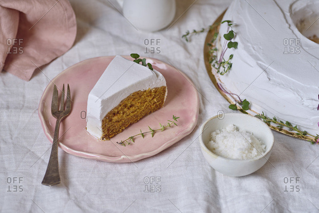 Top view shot of vegan carrot cake with coconut cream frosting with one slice cut and served separately on a plate