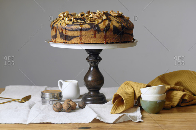 Vegan marble cake with walnuts  on wooden cake stand