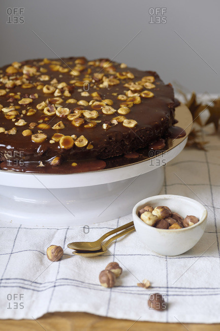 Vegan brownie cake with hazelnuts and salted caramel n white cake stand