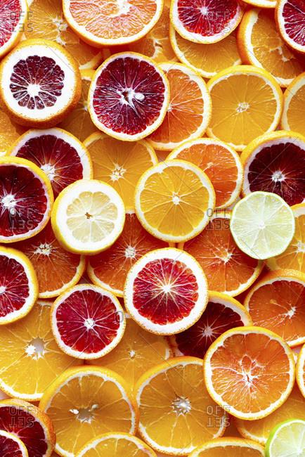 Variety of sliced citrus fruits on white background