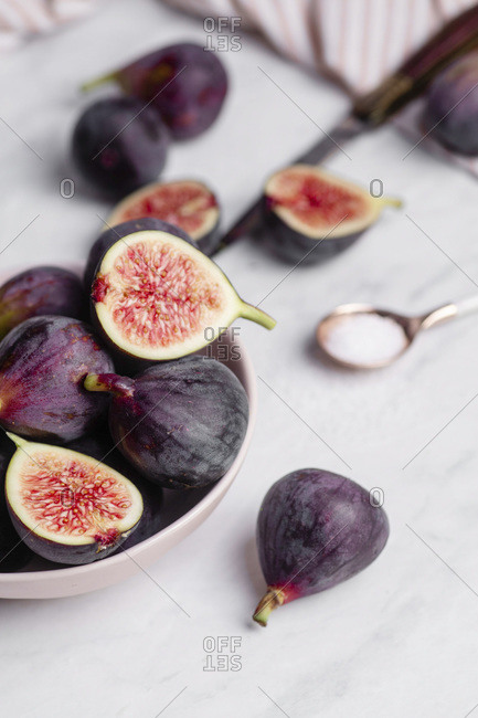 A bowl of whole and halved purple figs on a white marble countertop.