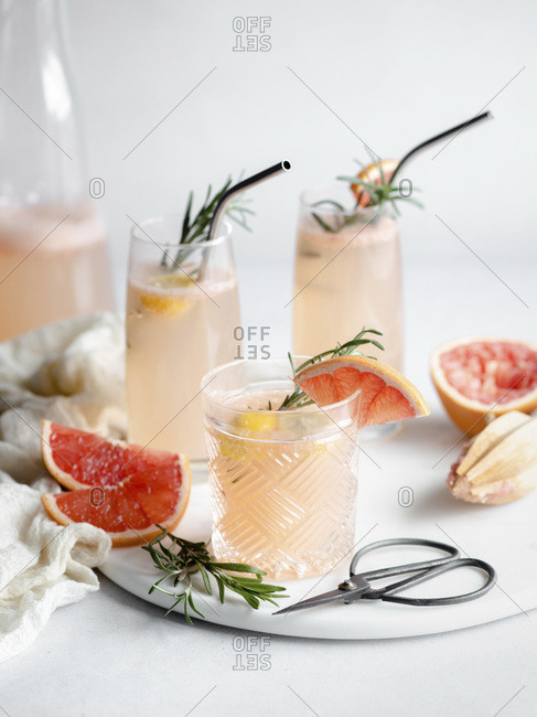 3 glasses of grapefruit cocktail on a marble tray with rosemary and grapefruit slices