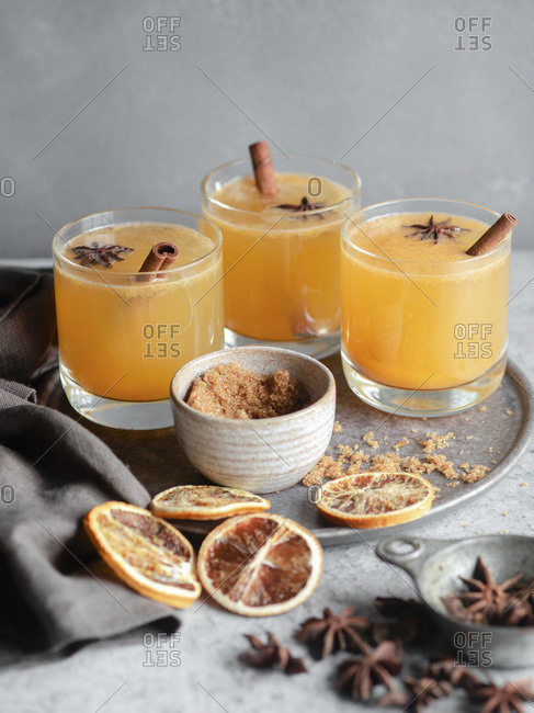 Three glasses of an orange spiced drink on a grey background, garnished with cinnamon sticks, brown sugar, blood oranges, and star anise.