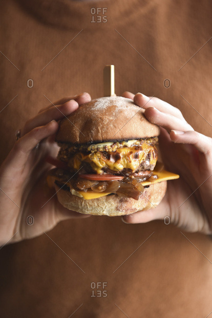 A burger on a plate, stacked in a burger bun