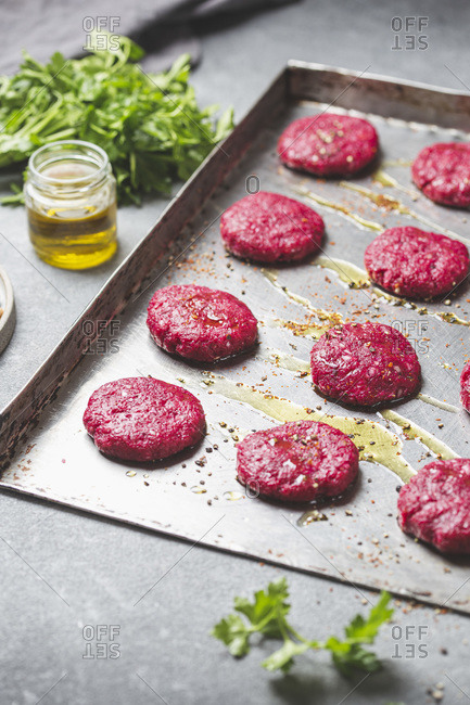 Uncooked red Beetroot burgers on metal tray