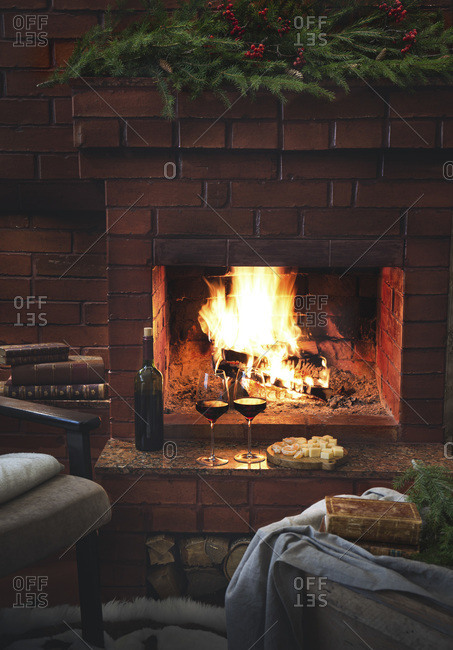 Holiday winter fireplace, red wine and cheese.