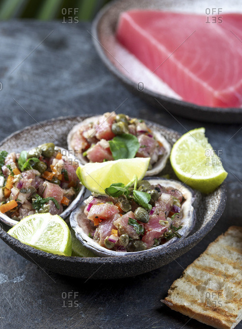 Raw tuna tartare served in seafood shells with lemon