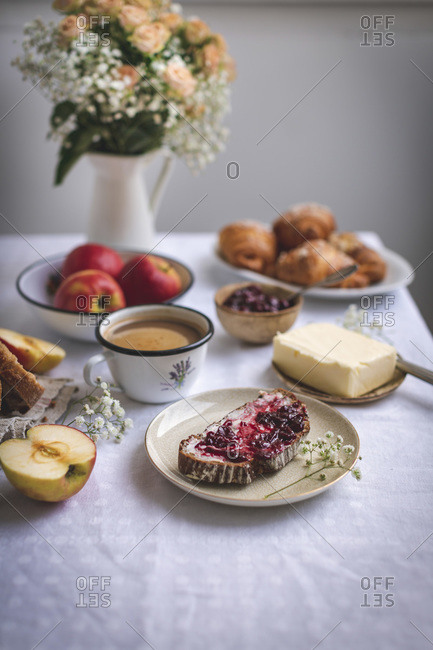 Bread with butter and jam, croissants, apples and coffee served for breakfast on a white linen tablecloth