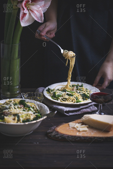 Woman eating spaghetti with kale, green peas, pancetta and Parmesan cheese served on a plate on a rustic wooden table