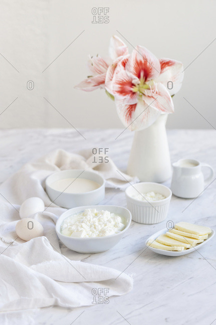 Fresh cheese, milk, cream and white eggs on a white marble table