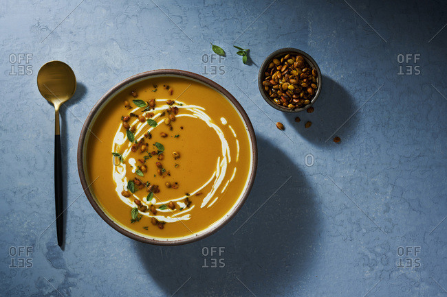 Bowl of butternut squash soup on a rustic, blue surface. Garnished with cream, roasted pepitas and fresh oregano.