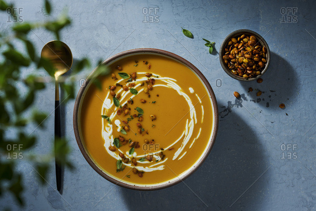 Large bowl of butternut squash soup on a rustic blue surface. Topped with roasted pepitas, cream and fresh oregano.
