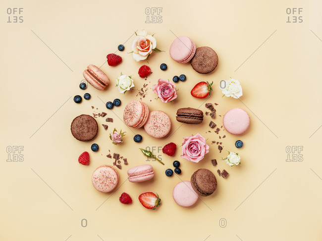 Round composition with French macarons, flowers and berries on cream yellow background.