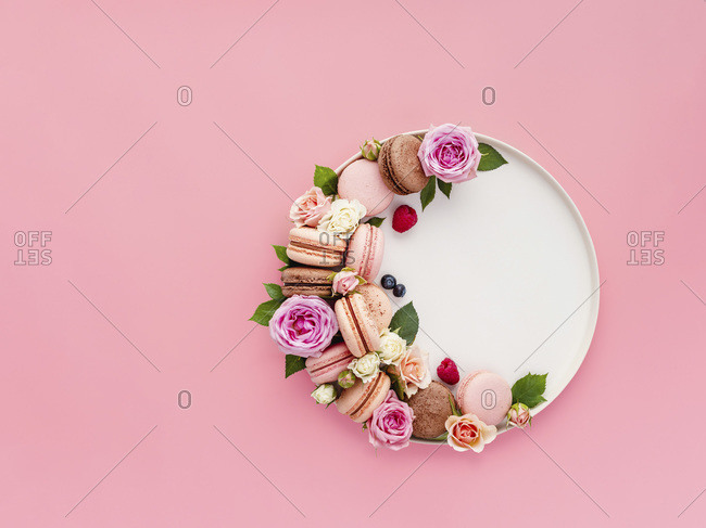 Beautiful composition with French macarons, flowers and berries on craft plate over pink background.