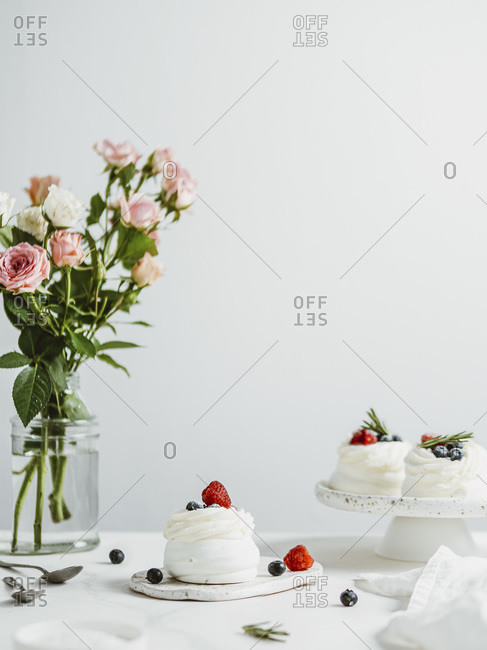 Mini Pavlova cakes with fresh berries and rosemary on white marble tabletop with flowers in glass vase bottle and white wall background.
