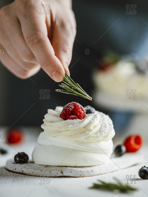 Female fingers holds rosemary to decorate mini Pavlova cake with fresh berries.