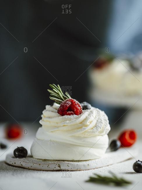 Mini Pavlova cake with fresh berries and fresh green rosemary.