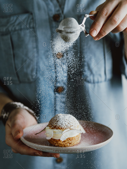 Woman in blue denim shirt holds with one hand pink plate with choux au craquelin pastry and sprinkles with her other hand icing sugar through a sieve.