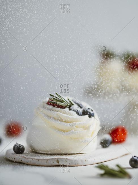Icing sugar sprinkles on mini Pavlova cake with fresh berries and fresh green rosemary.