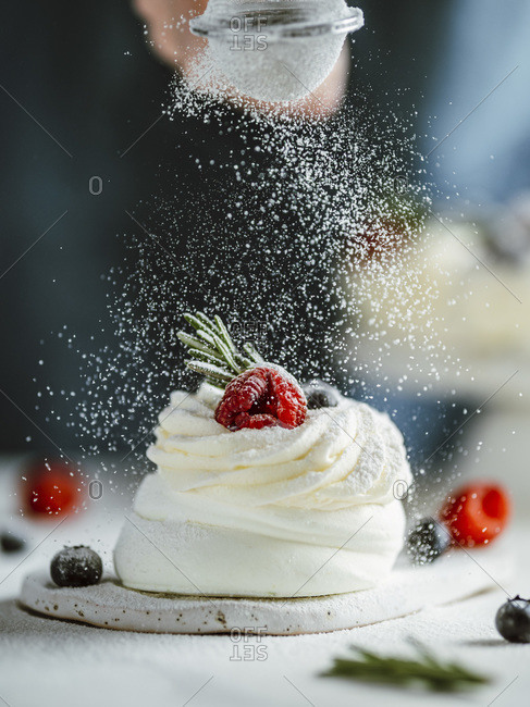 Woman sprinkles icing sugar through a sieve's on mini Pavlova cake decorated fresh berries and rosemary.