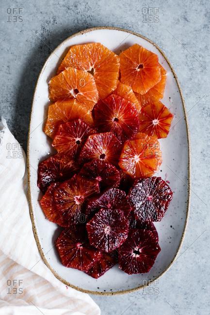 Sliced blood oranges on a ceramic plate