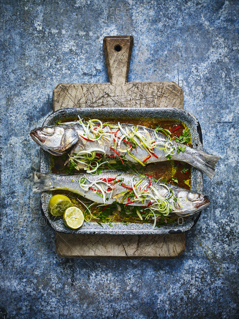 Baked sea bass on a baking tray and wooden chopping board, against a blue background