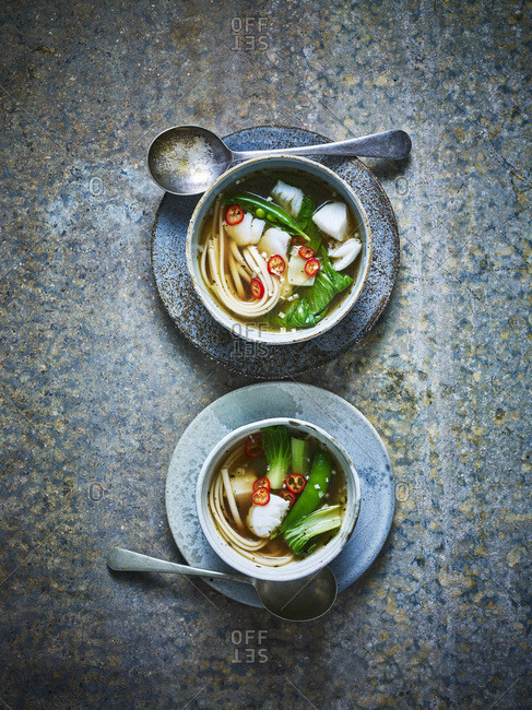 Noodles with bok choy, tofu and fish in a ceramic bowl on a blue background