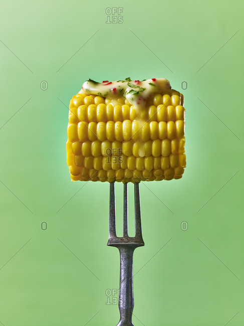 Corn on the cob with melted butter dripping, on a fork, against a green background