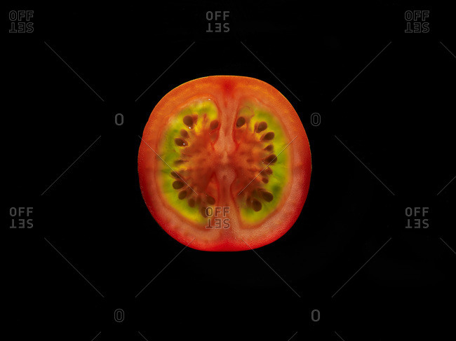 Backlit portrait of a red cherry tomato slice