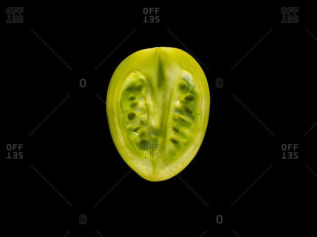 Backlit portrait of a green tomato slice