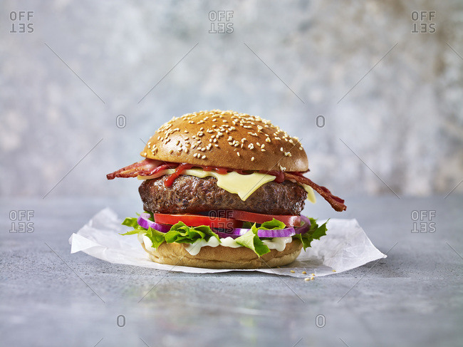 A beef burger with bacon against a light background in a sesame seed bun