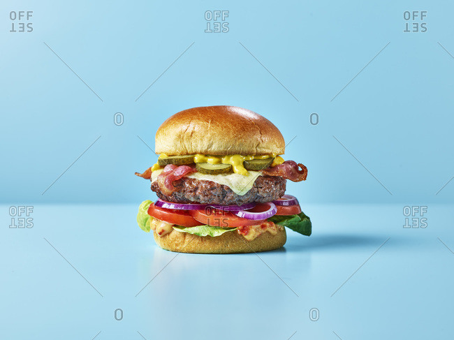 A cheese burger with bacon, salad, relish and gherkins against a blue background