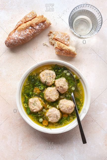 Chicken meatball soup with herbed broth in a bowl