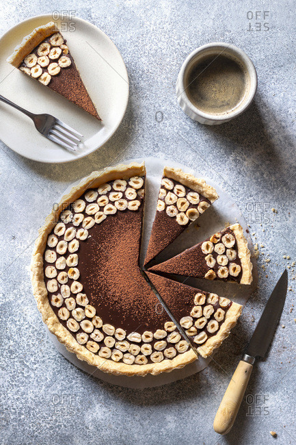 Chocolate hazelnut tart and a cup of coffee on the table.