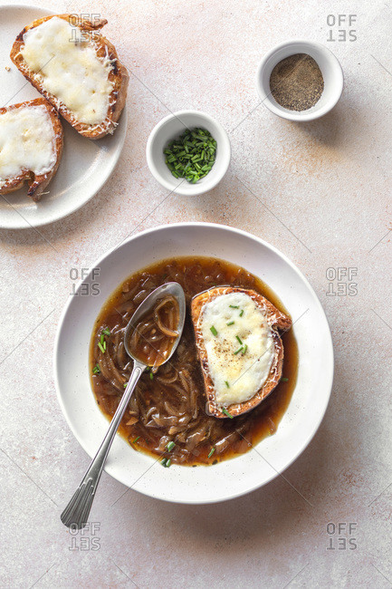 A bowl of French onion soup on the table.