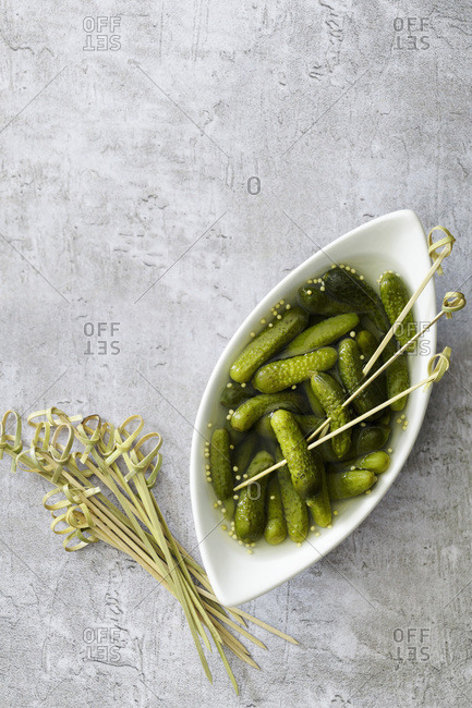 Pickled gherkins on bamboo skewers.