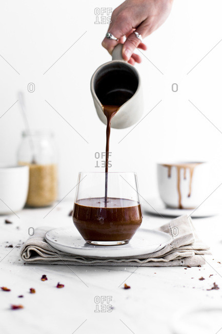 Woman pouring hot chocolate into a glass