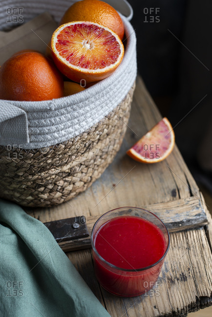 Basket with blood oranges an a wooden table with a glass of red orange juice