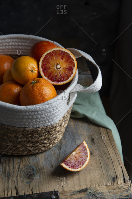 Basket with blood oranges an a wooden table