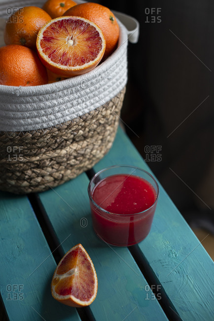 Blood oranges basket on a blue wood table with a glass red orange juice