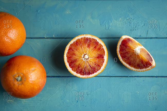 Overhead view of Sliced blood oranges on a blue wood table